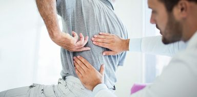 Older gentleman at the doctor's office getting his back examined by a doctor